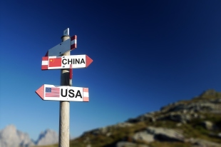 USA and Chinese flags on mountain signpost.