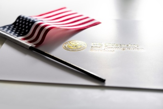 U.S. Citizenship and Immigration Services envelope, white folder for naturalization certificate on table with American flag